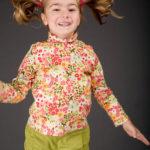 Mädchen springt und hat Spaß an der Fotografie - Kinderfotos Fotograf Peter Roskothen